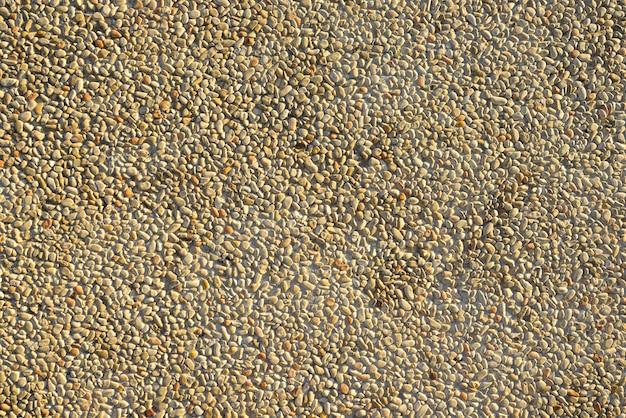 Pebbles pathway in concrete background of floor tiles.