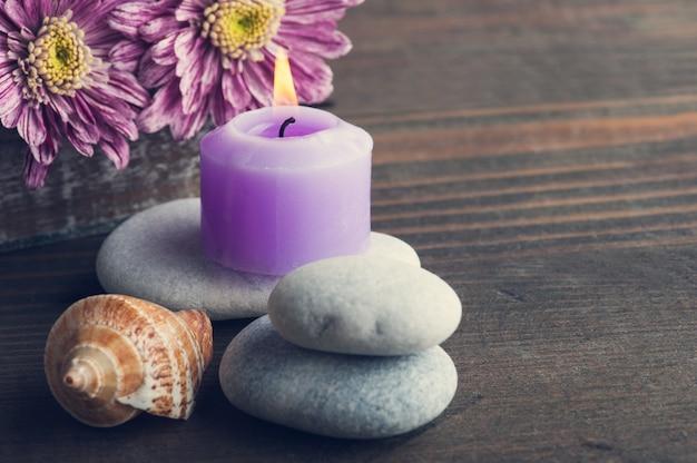 Pebbles, purple lit candle, flowers, shells