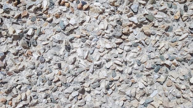 Галька щебень в цементном дворе. грязный треснувший старый гранж винтажный светло-серый бетон и цементная плесень текстура стены или фон пола с выветриваемой краской и царапинами.
