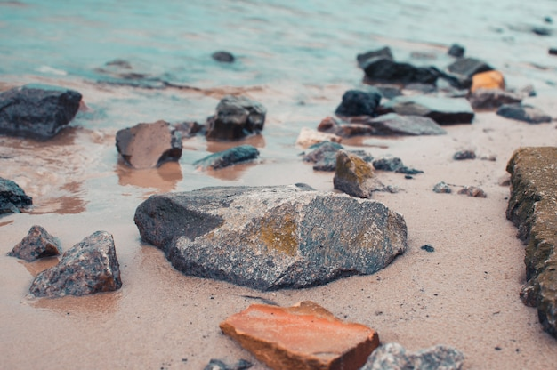 Pebbles on a sandy shore in clear water. the silky waves of a blue lake hit the stones. natural background.