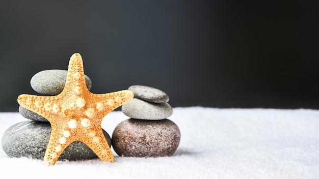 Pebbles stack with starfish, balance, pyramid of stones for meditation, stack of zen stones