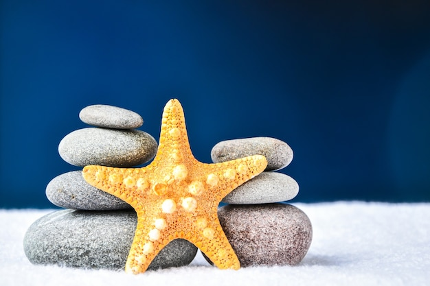 Pebbles stack with starfish, balance, pyramid of stones for meditation