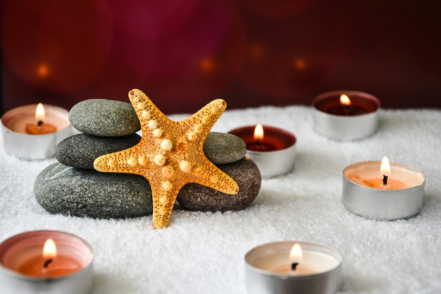 Pebbles stack with starfish candles, balance, pyramid of stones for meditation, stack of zen stones