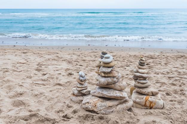 Ciottoli impilati l'uno sull'altro in equilibrio sulla spiaggia