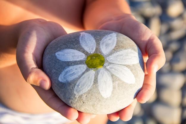 子供の手にデイジーが描かれた小石