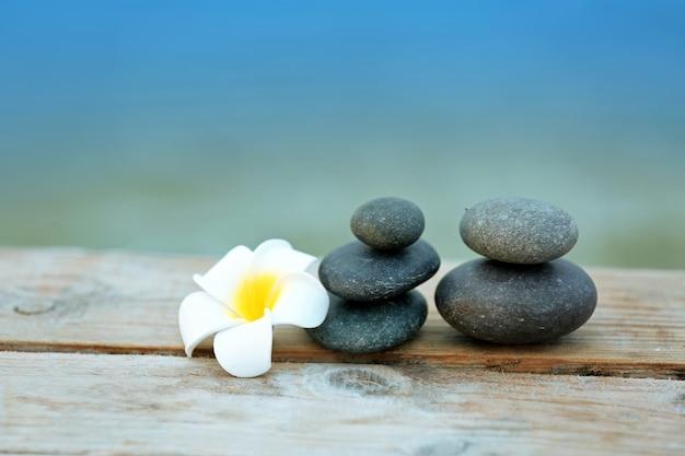 木製のテーブルにプルメリアの花が付いている小石