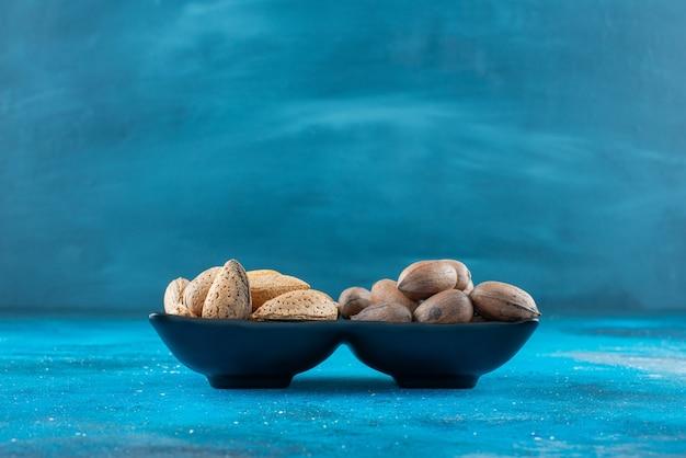 青い表面のボウルにピーカンナッツとアーモンド