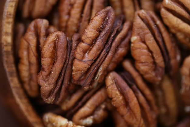 木製のボウルにピーカンナッツのクローズアップ。健康的な脂肪。