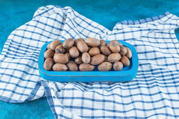 青いテーブルの上に、ティータオルの上の木のプレートのピーカンナッツ。