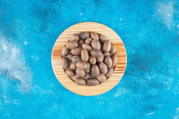 青いテーブルの上の木の板のピーカンナッツ。