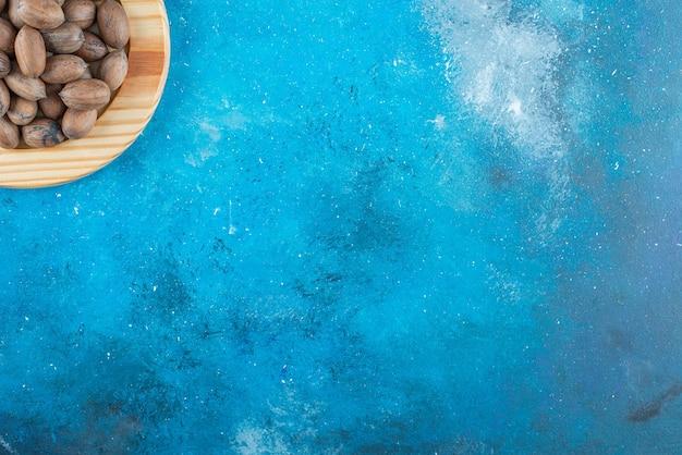 파란색 테이블에 나무 접시에 피칸 너트.