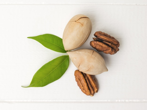 Pecan nuts with two leaves on a white wooden table. vegetarian food.