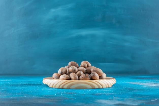 Noci pecan su un piatto di legno sulla superficie blu