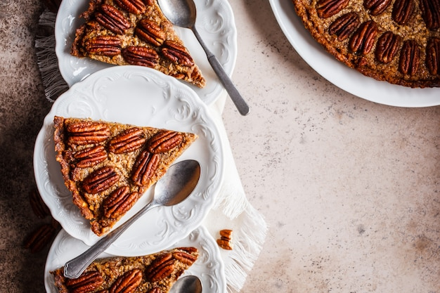 Pecan pie pieces on gray-brown background, flat lay. vegan dessert concept.