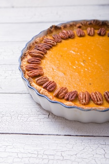 Pecan, pumpkin, thanksgiving holiday pies on a rustic table with decorative gourds. top view