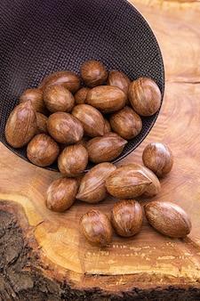 暗いカップから木製のテーブルに注がれたピーカンナッツ