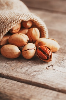 Pecans are spilled out of a burlap bag onto a wooden table in close-up.