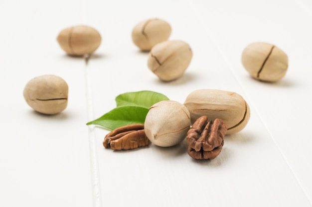 Pecans and green leaves on a white wooden table. vegetarian food.