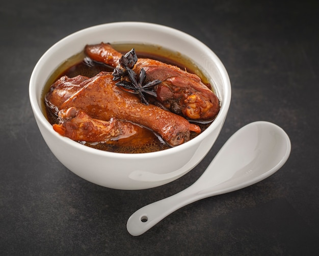 Ped pa lo, brown chinese stewed calf of duck leg in white bowl with white ceramic spoon on dark gray, grey, thai food