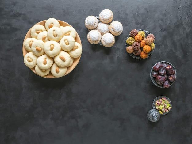 ペダ(インドの甘い)、黒いテーブルのミルクファッジ。 eid and ramadan dates sweets-アラビア料理。