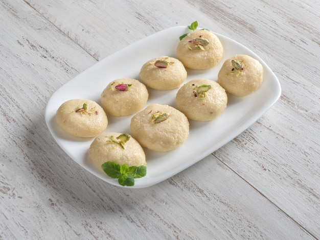 Peda (indian sweet), milk fudge in a white wooden table.