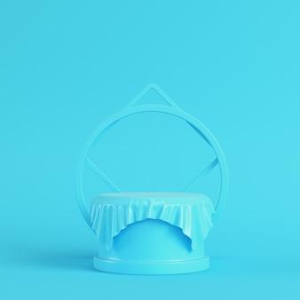 パステルカラーの明るい青色の背景に幾何学的な形の生地で覆われた台座