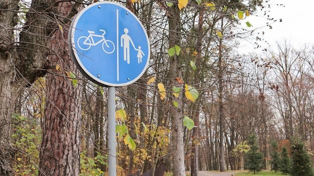 가을 공원의 나무와 푸른 하늘 배경에 흰색 파란색 표시가 있는 보행자 및 자전거 도로 표지판. 보행자와 자전거 이용자를 위한 별도의 차선.