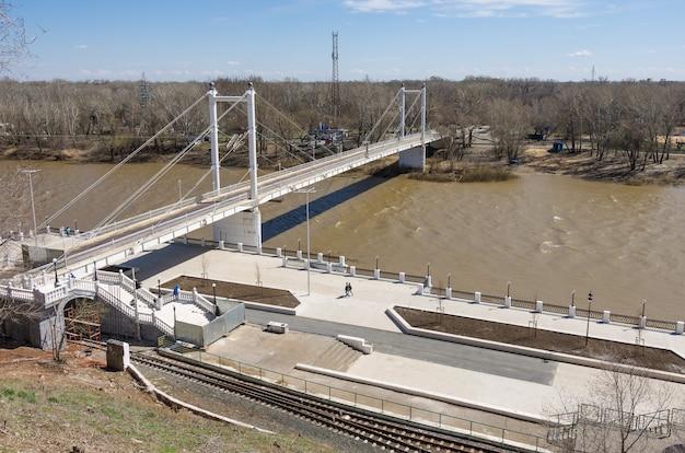 オレンブルク市のロシアの春の歩道橋の堤防とウラル川