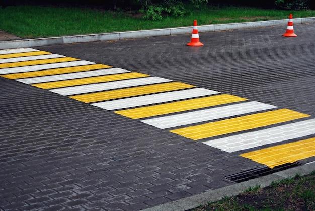 雨の日の舗装道路の横断歩道とトラフィックコーン