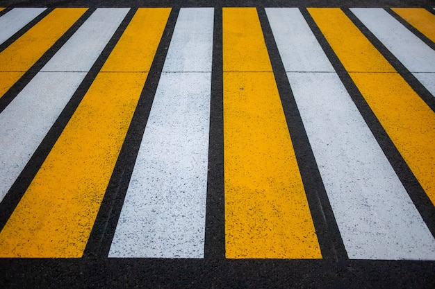 Pedestrian crossing on an asphalt road in the rays of the setting sun.