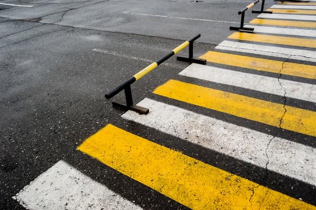 Пешеходный переход возле парковочных мест, белых и желтых полос.
