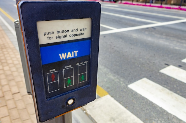 Pedestrian crossing push button on a post in a street