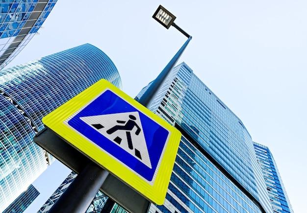 Знак пешеходного перехода у здания небоскребов города на фоне в москве, россия