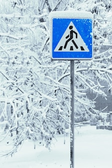 Pedestrian crossing sign in wintertime with trees covered with snow after snowfall on the surface