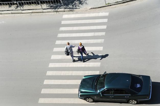 Пешеходный переход. вид сверху. ивано-франковск. украина-23.05.2017. люди переходят улицу. автомобиль идет по пешеходному переходу.