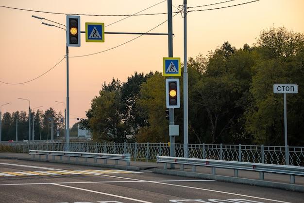 Pedestrian crossing with traffic lights across an asphalt road