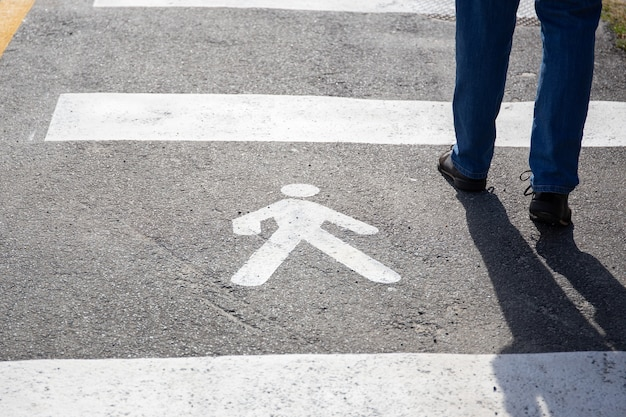 Pedestrian sign on the asphalt and human legs walking on sunny day