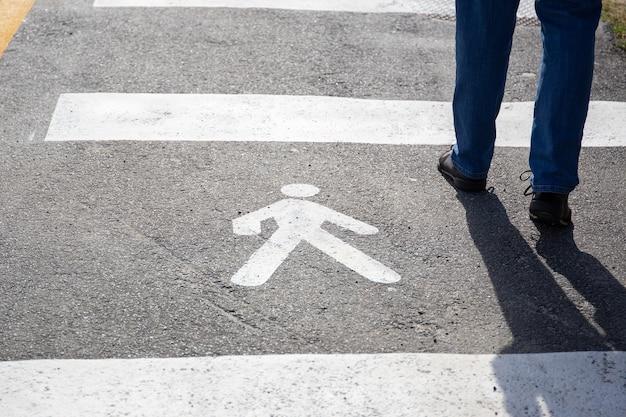Пешеходный знак на асфальте и человеческие ноги, идущие в солнечный день