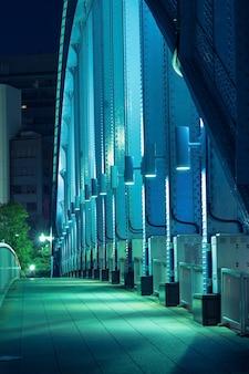 Pedestrian way along the metallic arc structure of city bridge illuminated by night