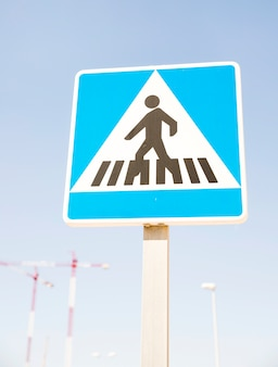 Pedestrians warning sign against blue sky