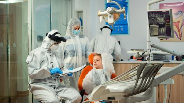 Ppeスーツを着た小児歯科医と看護師は、子供の患者に質問し、検査する前にクリップボードにメモを取ります。つなぎ服を着て新しい通常の歯科医院で働く口腔病専門医と助手