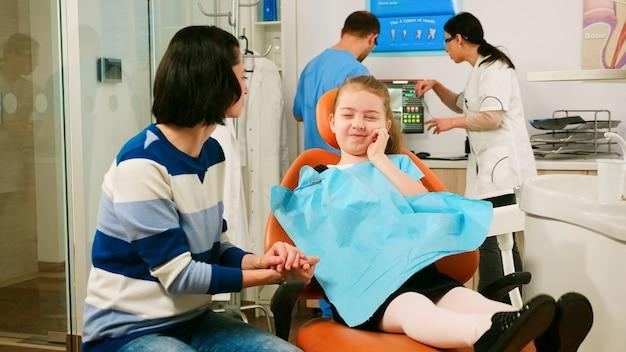 소아 치과 의사는 백그라운드에서 남자 조수와 이야기하는 아이 환자의 치아 엑스레이를 검사합니다. 구강 의자 치과 단위에 앉아 어머니에게 영향을받는 질량을 보여주는 슬픈 아이.