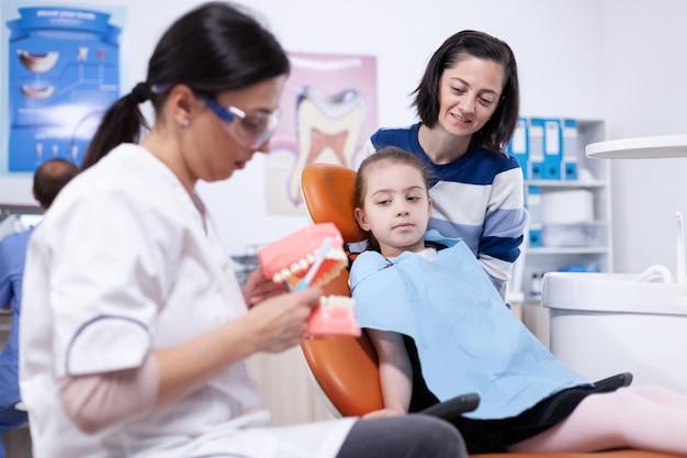 Детский стоматолог обучает маленькую девочку правильной чистке зубов. маленькая девочка и мать, слушая стоматолога, говорят о гигиене зубов в стоматологической клинике, держа модель челюсти.