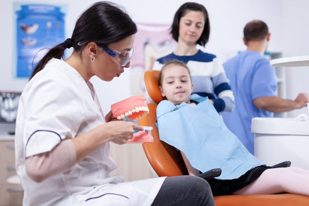 Pediatric dentist holding jaw model explaining cavity to child wearing bib. little girl and mother listening stomatolog talking about tooth hygine in dentistiry clinic holding jaw model.