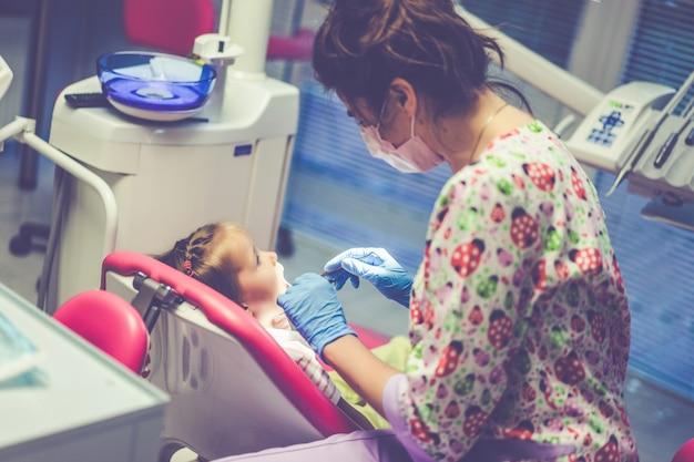 Детский стоматолог. маленькая девочка на приеме у стоматолога.