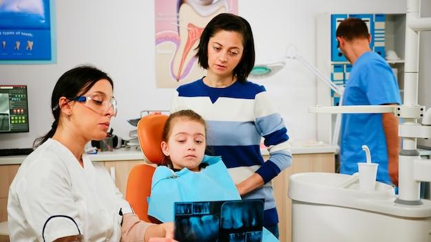 小児歯科医は、男性助手が手術用の滅菌ツールを準備している間、影響を受けた歯を指しているレントゲン写真を保持している歯科の問題を示しています。口腔病学ユニットで働く医師と看護師