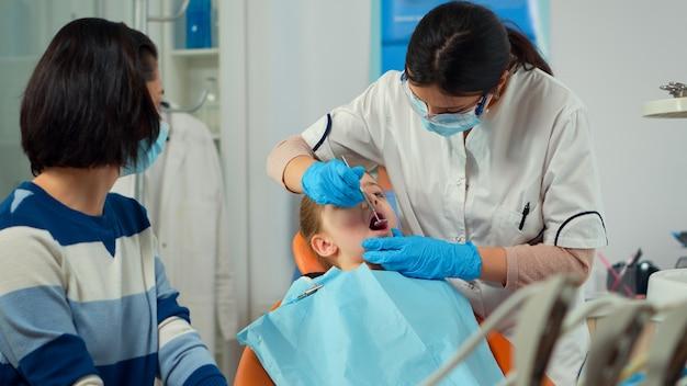 口を開けて口腔病学の椅子に横たわっているクリニックの小さな女の子の患者に歯を治療している小児歯科医。保護マスクを着用して口腔病棟で一緒に働く医師と看護師