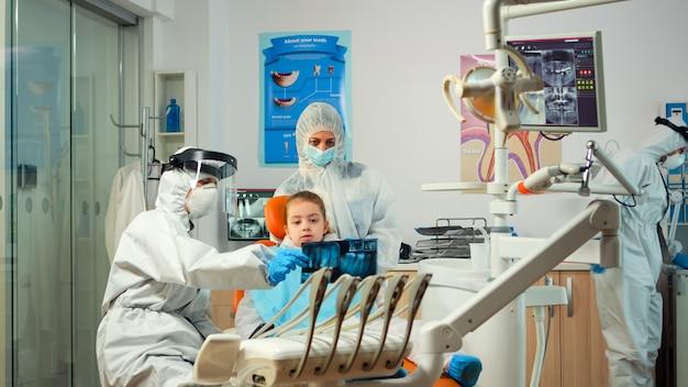 歯のx線写真を示す新しい正常な口腔病学ユニットで少女患者を治療する防護服を着た小児歯科医。フェイスシールドカバーオール、マスク、手袋を着用し、x線撮影を説明する医療チーム