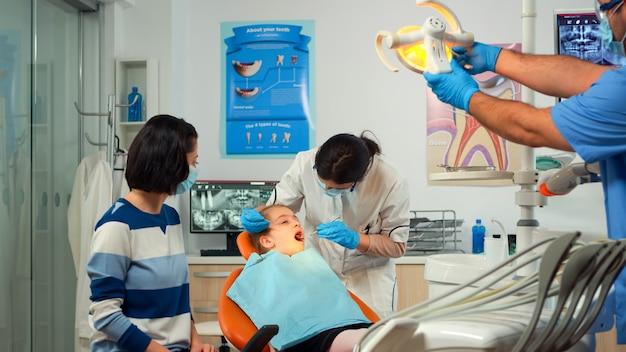 口腔病学の椅子に座っている少女の歯の健康状態をチェックするマスクを持った小児歯科医、滅菌された歯科用器具を使用している医師、現代の口腔病学ユニットの男性看護師と協力しています。