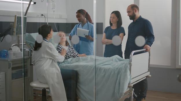 아프리카계 미국인 간호사가 iv 드립을 확인하는 동안 소아과 의사가 호흡곤란 증상을 검사합니다...